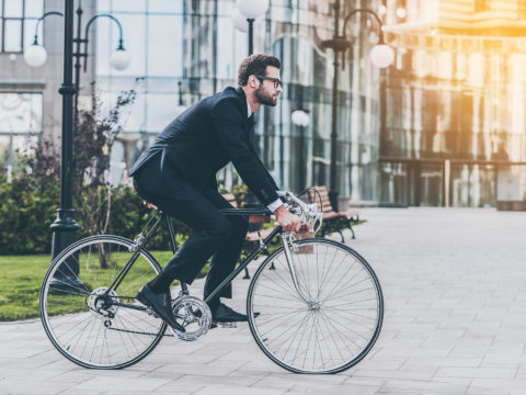 Side view of young businessman looking forward while riding on his bicycle
